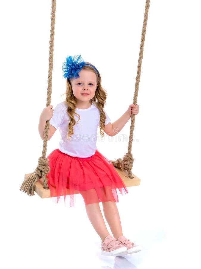 Petite fille balançant sur une oscillation photographie stock