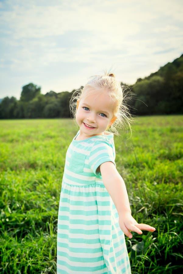 Petite fille blonde adorable avec le sourire effronté, dehors photographie stock