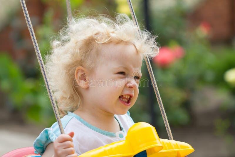 Petite fille blonde adorable de cheveux bouclés ayant l'amusement sur une oscillation photos libres de droits