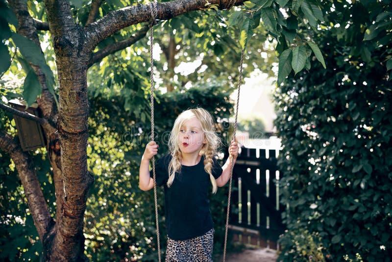 Petite fille blonde adorable jouant dehors sur une oscillation d'arbre image stock