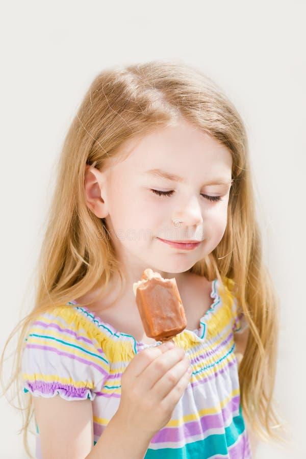Petite fille blonde adorable mangeant de la glace photos libres de droits