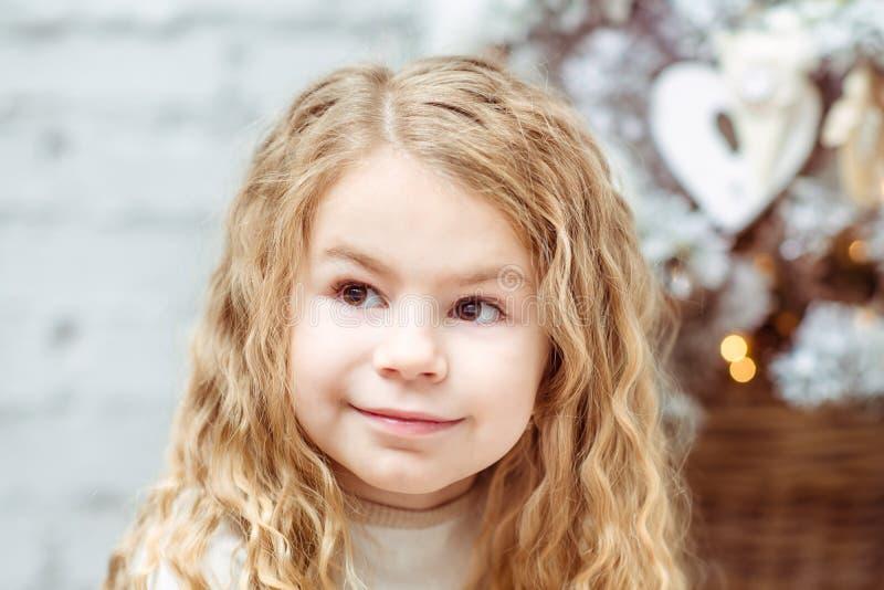 Petite fille blonde adorable s'asseyant sous l'arbre de Noël image libre de droits