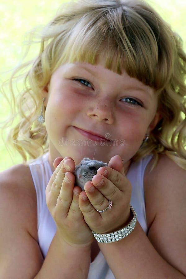 Petite fille blonde adorable tenant son hamster photo libre de droits