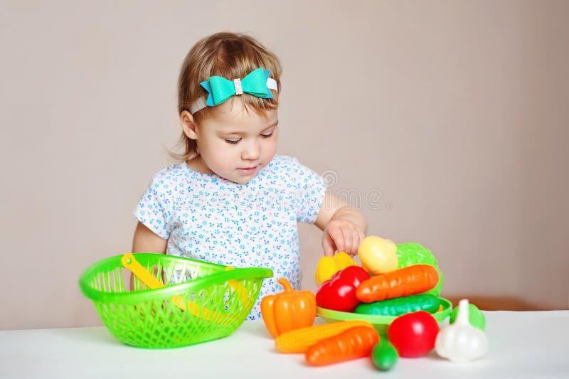 Petite fille blonde avec du charme dans une robe blanche d'été, se reposant à la table et aux jeux avec les jouets en plastique images libres de droits