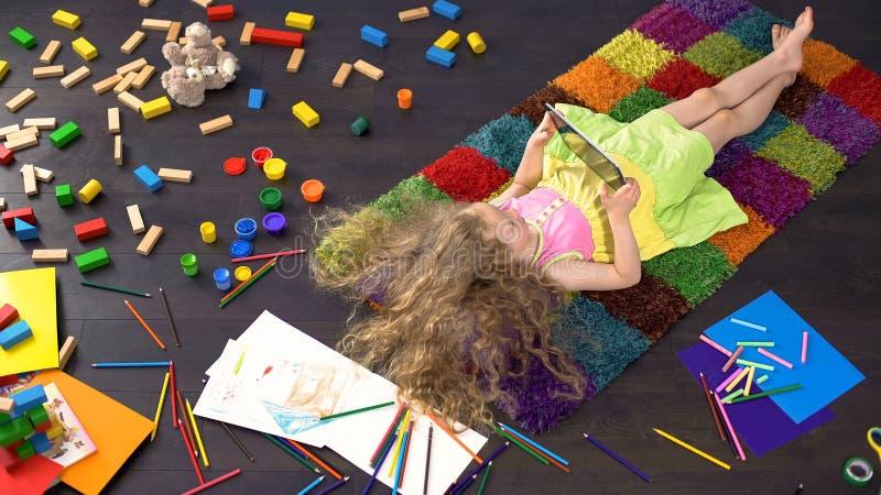 Petite fille blonde avec les cheveux blonds se trouvant sur le tapis coloré et jouant sur le comprimé images stock