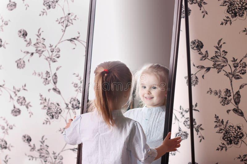 Petite fille blonde dans la chemise rayée regardant son reflectio photographie stock libre de droits
