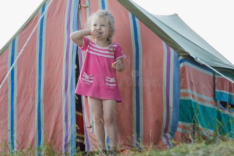 Petite fille blonde de campeur détendant près de la tente de toile rayée de vintage photographie stock libre de droits