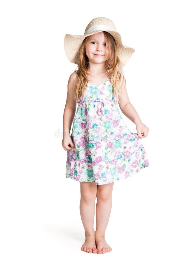 Petite fille blonde de sourire portant le grands chapeau et robe blancs image stock
