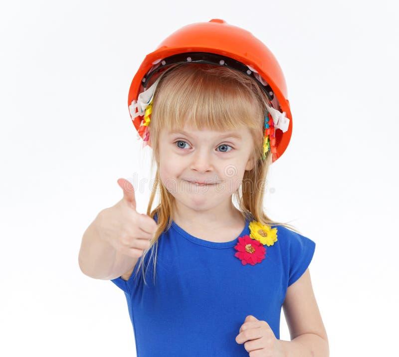 Petite fille blonde drôle avec deux queues dans le casque orange photos stock