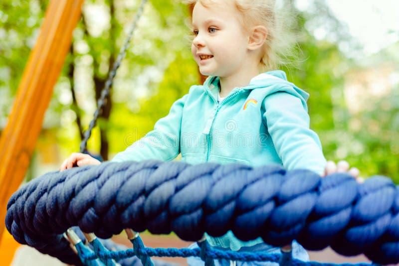 Petite fille blonde heureuse ayant l'amusement sur un terrain de jeu images libres de droits