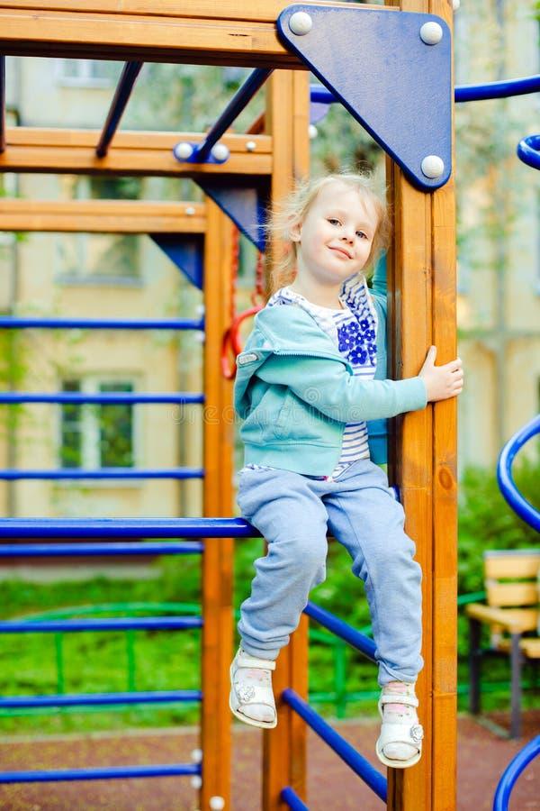 Petite fille blonde heureuse ayant l'amusement sur un terrain de jeu image stock