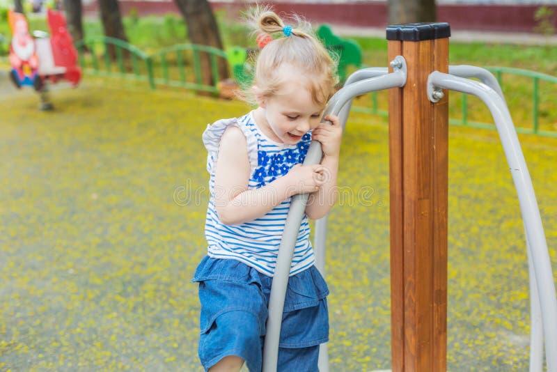 Petite fille blonde heureuse ayant l'amusement sur un terrain de jeu photo stock