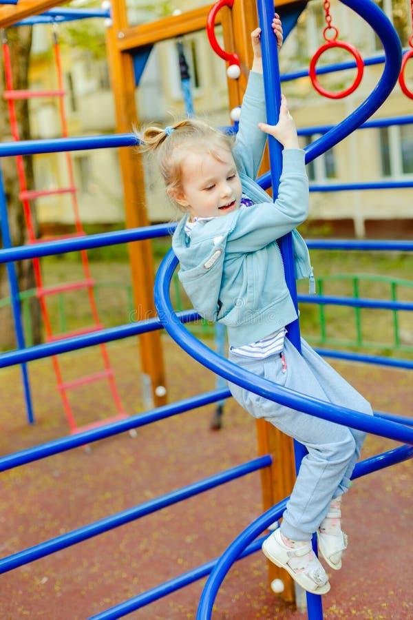 Petite fille blonde heureuse ayant l'amusement sur un terrain de jeu photographie stock libre de droits