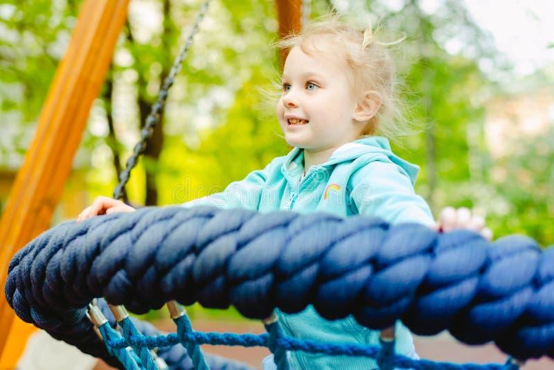 Petite fille blonde heureuse ayant l'amusement sur un terrain de jeu photos libres de droits