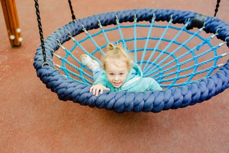Petite fille blonde heureuse ayant l'amusement sur un terrain de jeu photographie stock