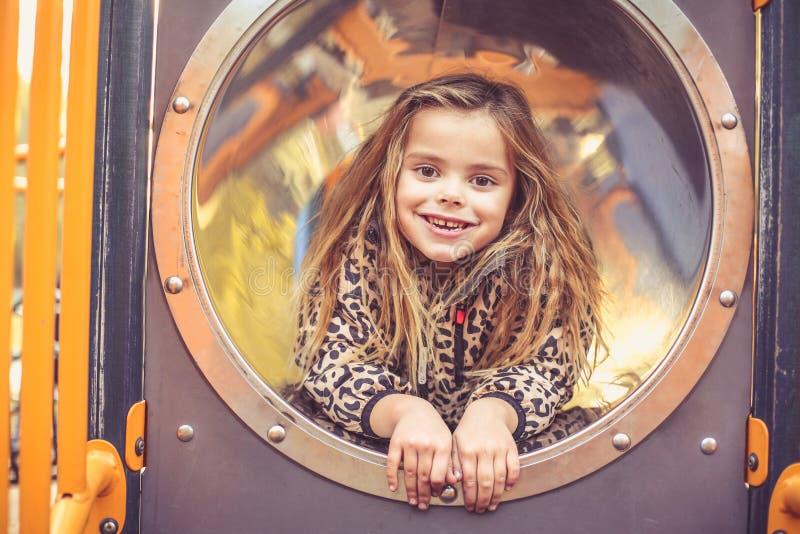 Petite fille blonde heureuse dans le terrain de jeu image stock