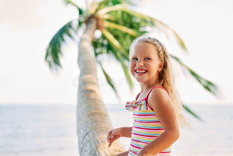 Petite fille blonde heureuse jouant sur la plage se reposant sur le palmier photographie stock