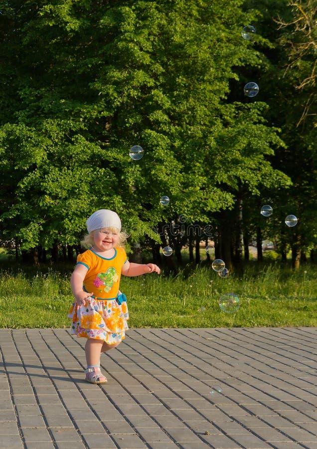 Petite fille blonde heureuse pendant l'été ayant l'amusement avec des bulles de savon dehors images stock