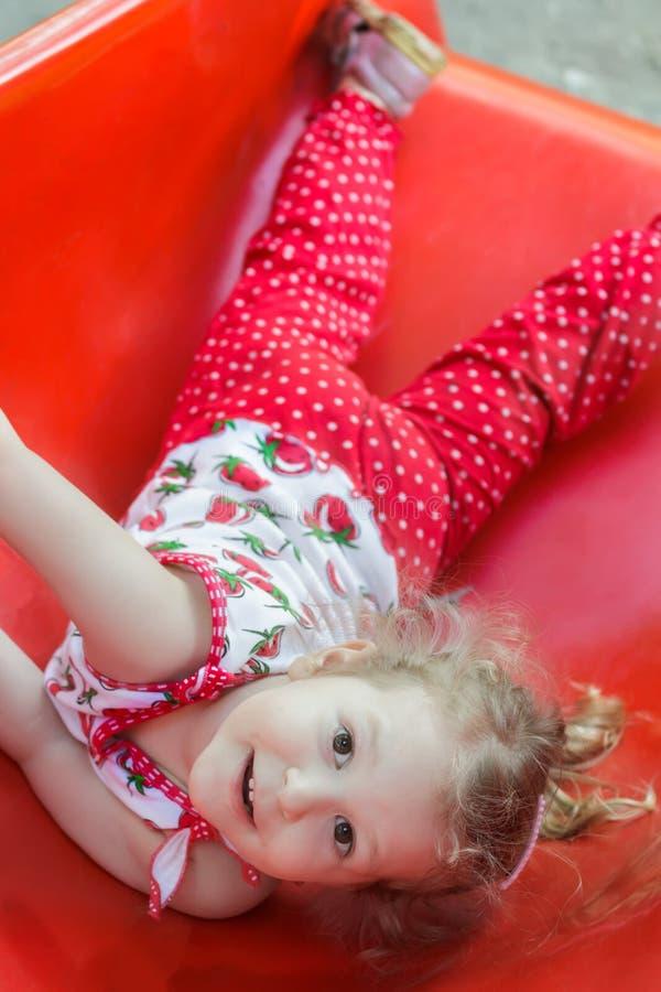 Petite fille blonde heureuse se trouvant sur la glissière en plastique rouge de terrain de jeu et regardant l'appareil-photo image stock