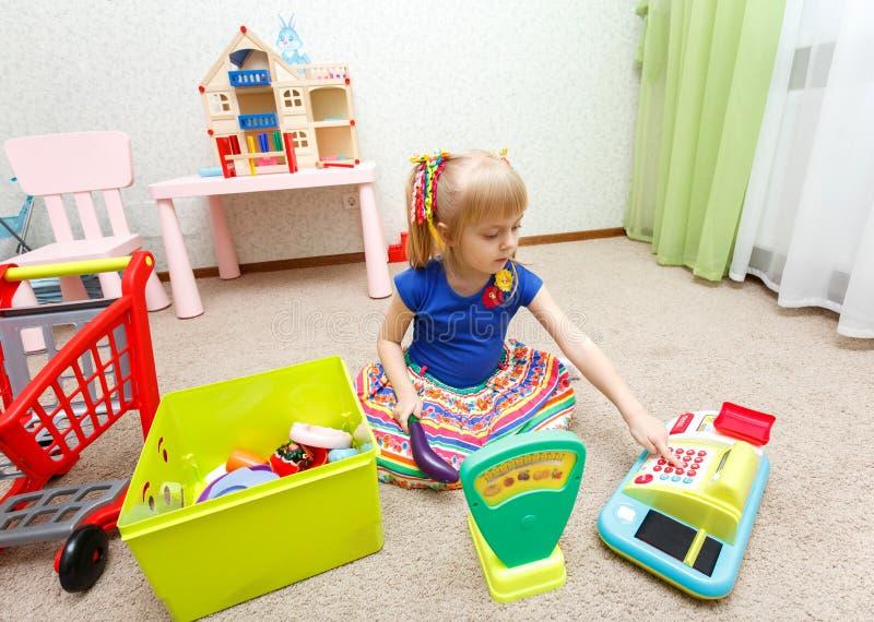 Petite fille blonde jouant le jeu de rôle avec la caisse enregistreuse de jouet images libres de droits