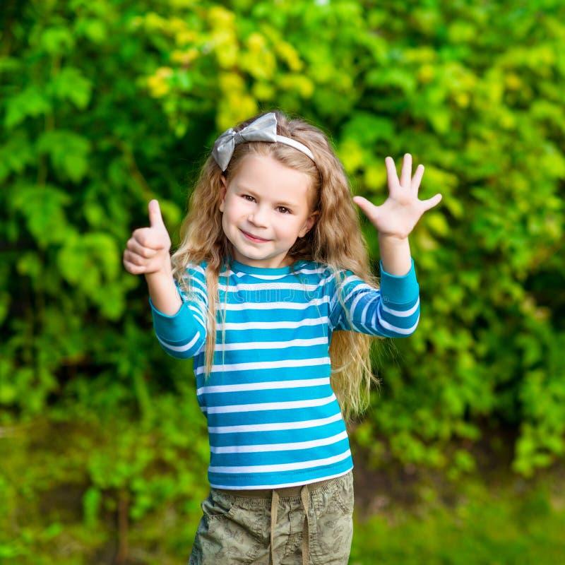 Petite fille blonde mignonne avec de longs cheveux bouclés montrant six doigts images stock