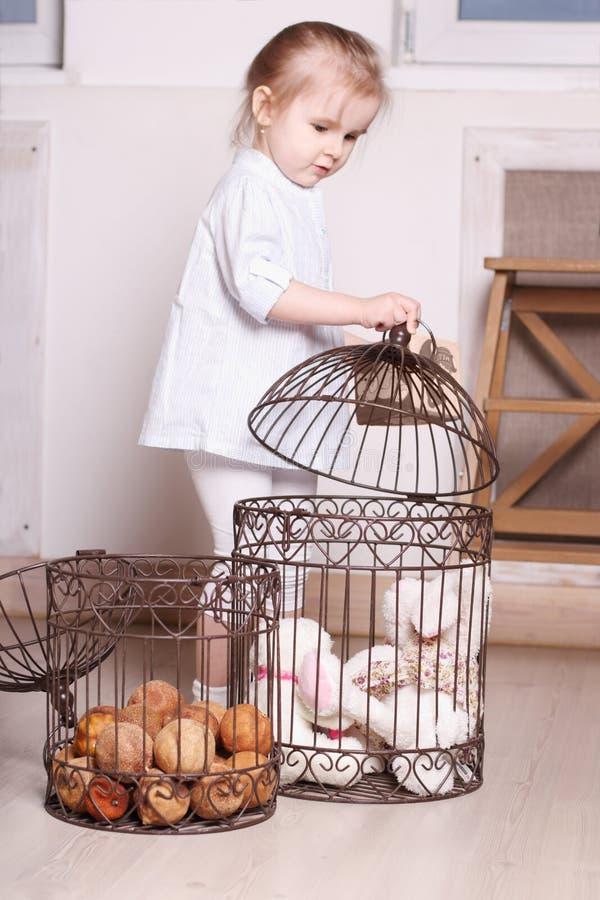 Petite fille blonde mignonne dans des supports de chemise rayée et des cages de jouer images stock