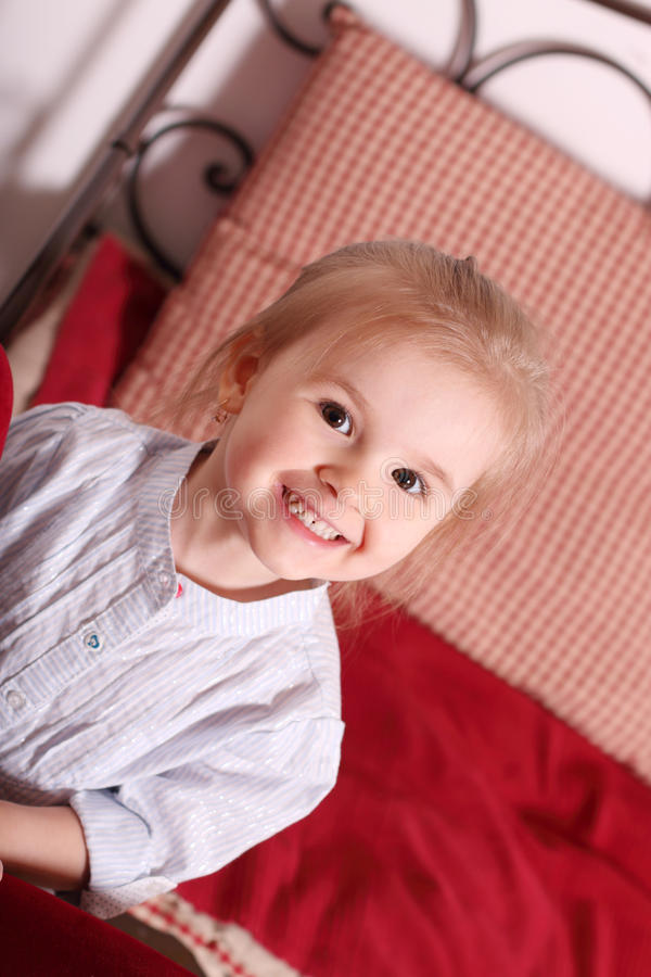 Petite fille blonde mignonne dans la chemise rayée se reposant parmi l'oreiller rouge photos stock