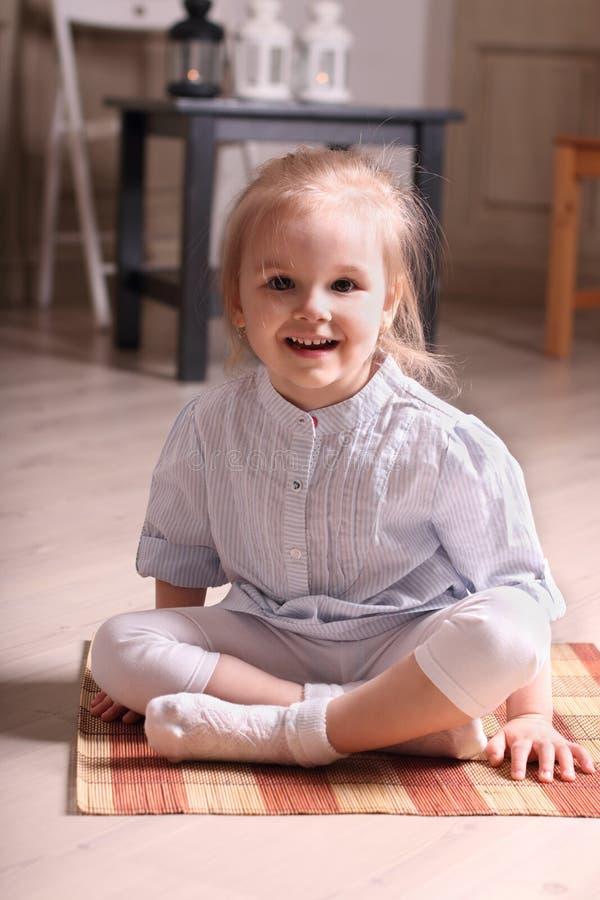 Petite fille blonde mignonne dans la chemise rayée se reposant sur le tapis et le smili photos libres de droits