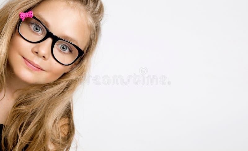 Petite fille blonde mignonne en verres sur un fond blanc dans images stock