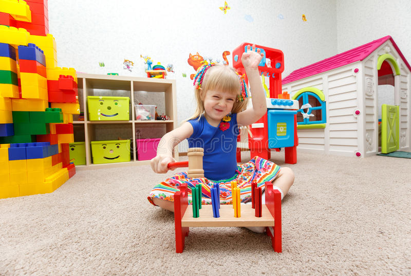 Petite fille blonde mignonne jouant avec le marteau de jouet photo libre de droits