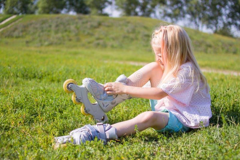 Petite fille blonde mignonne s'asseyant sur l'herbe verte et mettant sur des patins de rouleau - loisirs, enfance, jeux de plein  image stock