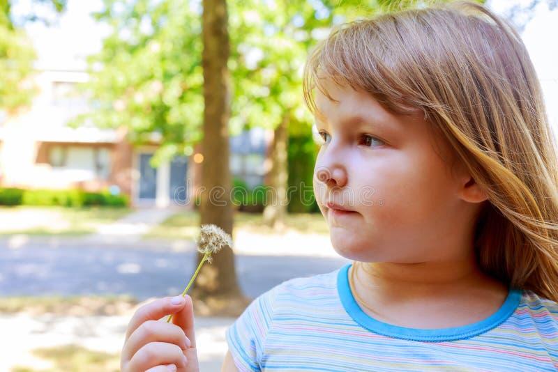 Petite fille blonde mignonne soufflant un pissenlit photo libre de droits