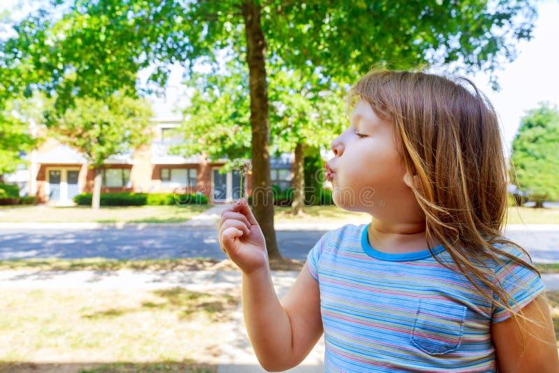 Petite fille blonde mignonne soufflant un pissenlit image stock