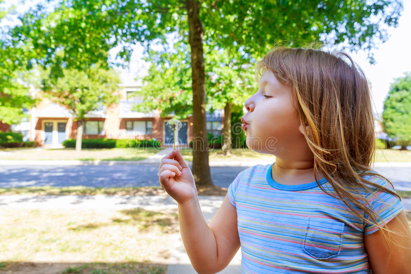 Petite fille blonde mignonne soufflant un pissenlit photographie stock