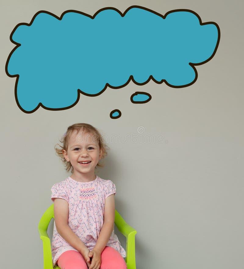 Petite fille blonde mignonne souriant et pensant à quelque chose Concept de dessin photos stock