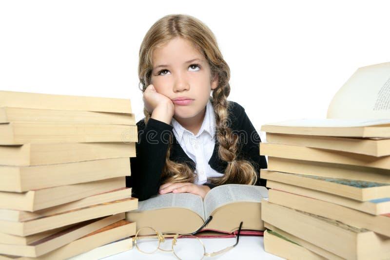 Petite fille blonde pensant avec des livres photos stock