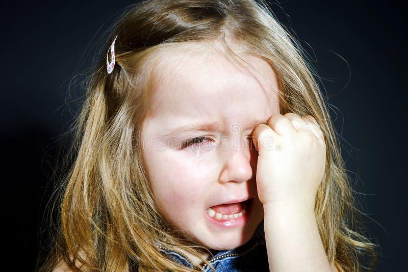 Petite fille blonde pleurante avec le foyer sur elle larmes images stock