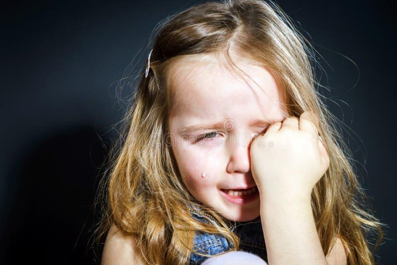 Petite fille blonde pleurante avec le foyer sur elle larmes photos stock