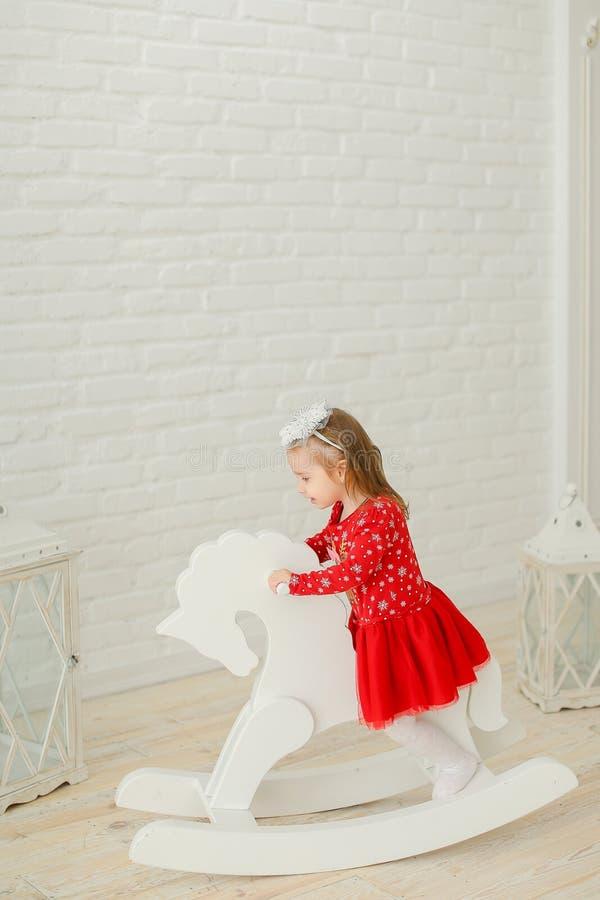 Petite fille blonde portant la robe rouge et jouant avec le cheval de basculage, mur de briques blanc à l'arrière-plan photographie stock