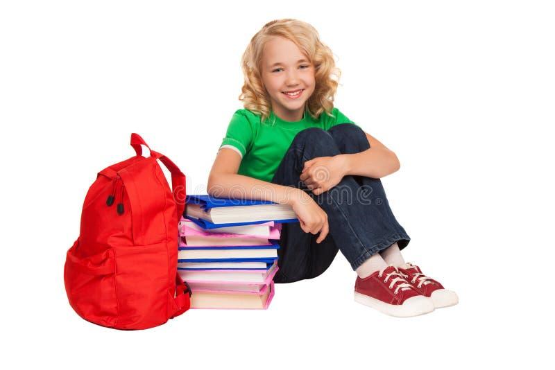Petite fille blonde s'asseyant sur le plancher près des livres et du sac photographie stock