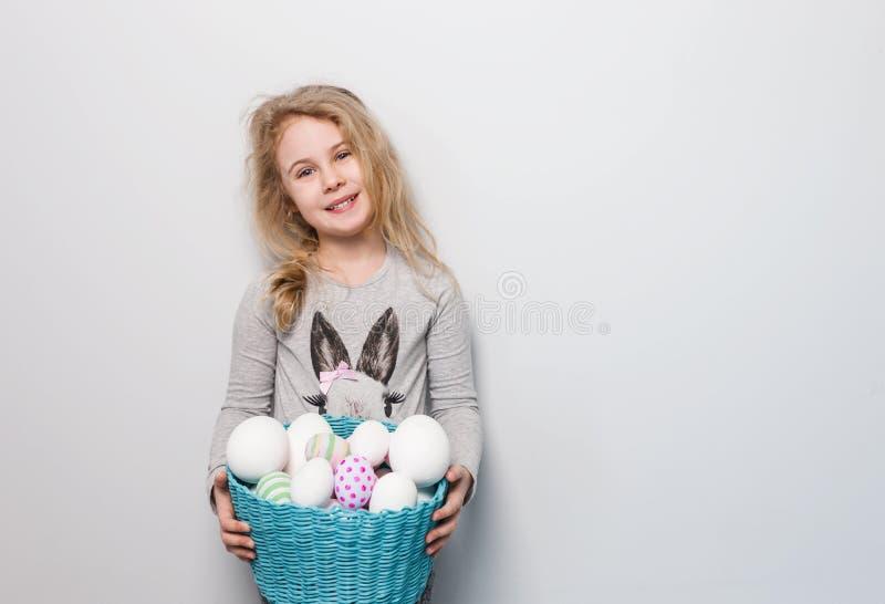 Petite fille blonde tenant le panier avec les oeufs peints Jour de Pâques image stock