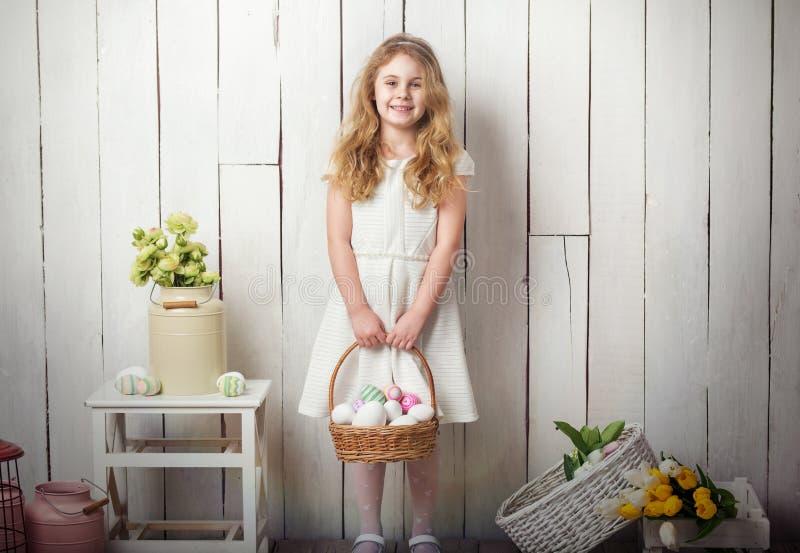 Petite fille blonde tenant le panier avec les oeufs peints Jour de Pâques images stock