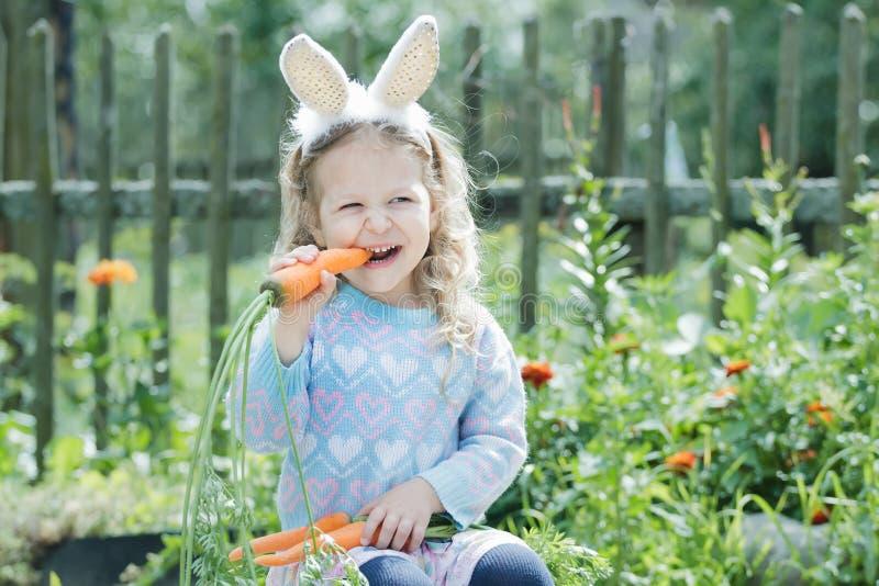 Petite fille blonde utilisant les oreilles drôles de lapin de DIY rongeant la carotte fraîche photographie stock libre de droits