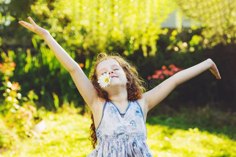 Petite fille bouclée avec la marguerite dans des ses dents reposant au printemps le parc photo stock