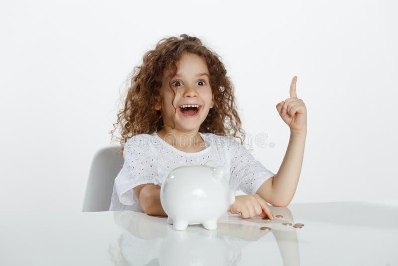 Petite fille bouclée mignonne assise à une table près de la tirelire, montrant à un doigt, au-dessus du fond blanc, l'espace de c images stock