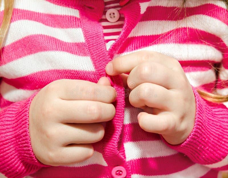 Petite fille boutonnant sa veste photo stock