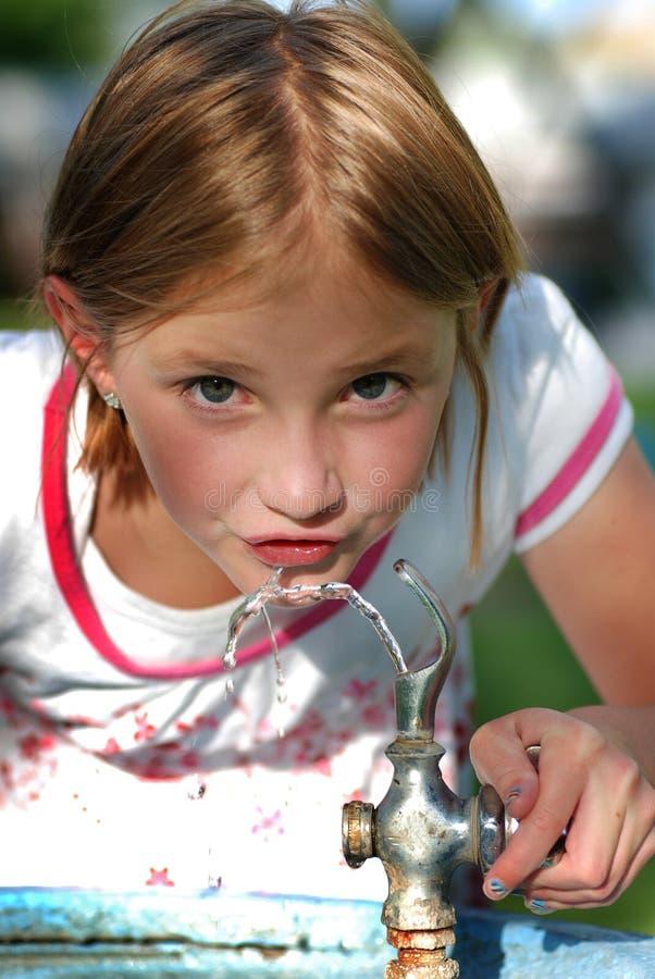 Petite fille buvant de la fontaine d'eau photos stock