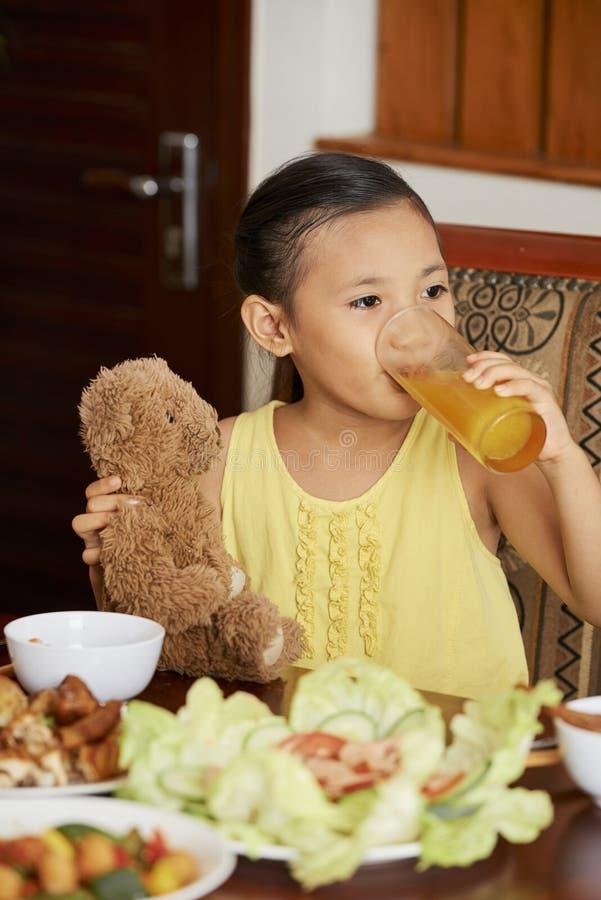 Petite fille buvant du jus d'orange photo libre de droits