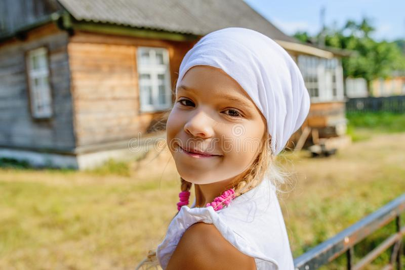 Petite fille calme dans l'écharpe blanche contre la maison rurale proche photographie stock libre de droits