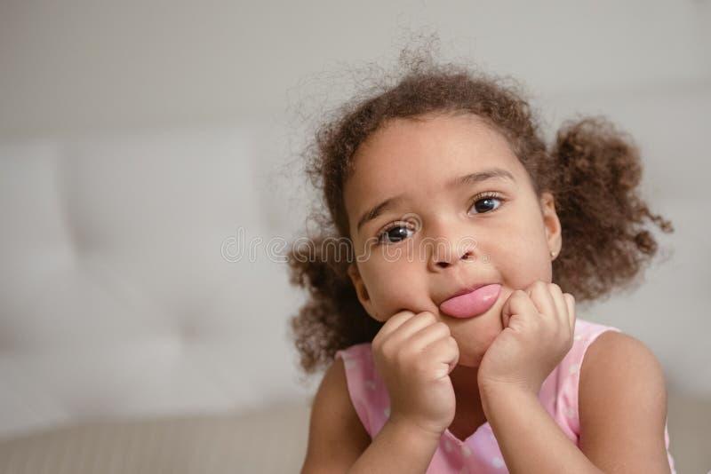 Petite fille caucasienne africaine mignonne, au-dessus de fond foncé images stock